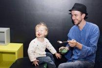 Father feeding toddler ice cream with spoon — Stock Photo