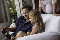 Семья с помощью цифрового планшета вместе дома — стоковое фото