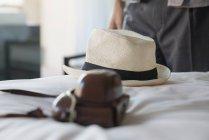 Kamera und Stroh Hut auf Bett im Hotelzimmer — Stockfoto