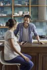 Schwangere Frau plaudert mit Mann in Küche — Stockfoto