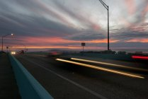 Light trails from traffic on highway at sunset — Stock Photo