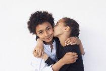 Portrait de frère et sœur embrassant sur fond blanc — Photo de stock
