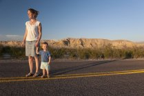 Mother and toddler son walking together on paved road through desert — Stock Photo