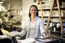 Retrato de empregado de restaurante em mesa de dinheiro — Fotografia de Stock