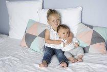 Дівчинка з молодший братик, сидячи на ліжку — стокове фото