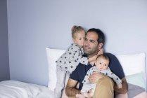 Père avec bébé garçon et jeune fille dans le lit — Photo de stock