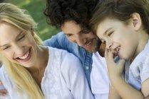 Família com uma criança juntos relaxante ao ar livre piquenique — Fotografia de Stock