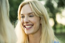 Portrait of smiling blonde woman outdoors — Stock Photo
