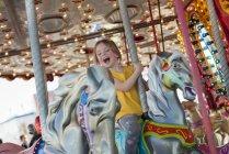 Glückliche kleine Mädchen reiten auf Karussell — Stockfoto
