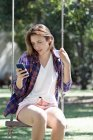 Young woman sitting on swing, looking at smartphone — Stock Photo