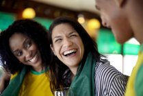 Women laughing in bar with male friend — Stock Photo