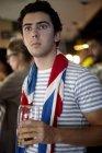 Fã de futebol britânico assistindo jogo no bar com bandeira drapeado em torno do pescoço e copo de cerveja — Fotografia de Stock