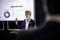 Donna che dà presentazione su schermo di proiezione — Foto stock