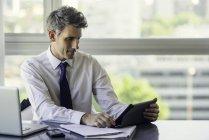 Homme à l'aide de tablette numérique au bureau — Photo de stock