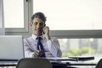 Человек в офисе разговаривает по телефону в офисе — стоковое фото