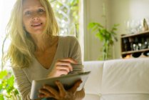 Mature woman using digital tablet at home — Stock Photo