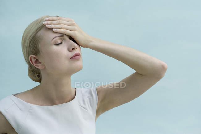 Mujer cogida de la mano en la cabeza, ojos cerrados - foto de stock