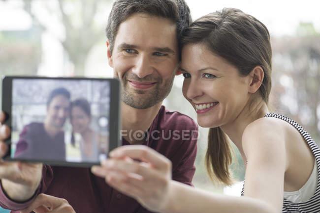 Couple à l'aide de tablette numérique de prendre un selfie — Photo de stock