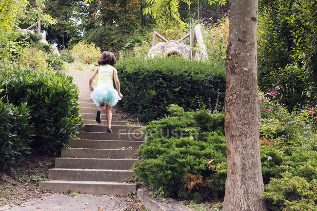 Girl in tutu running up stairs in park, rear view — Stock Photo