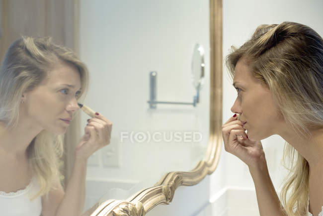Woman applying cosmetics in mirror — Stock Photo