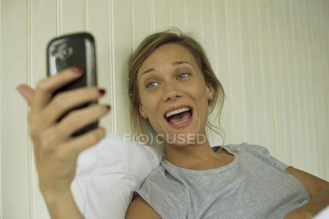 Lächelnde Frau nehmen Selfie im Bett — Stockfoto