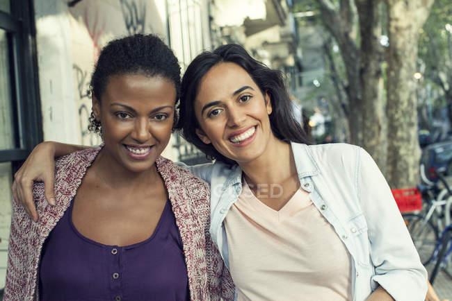 Жінки, друзі обіймаються на тротуарі кафе, портрет — стокове фото