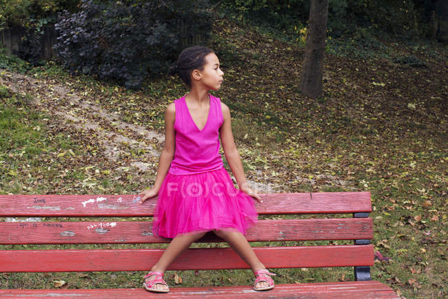 Girl sitting alone on park bench, looking away in thought — Stock Photo