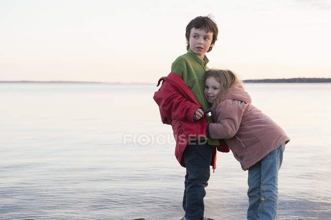 Little girl hugging her brother at water's edge — Stock Photo
