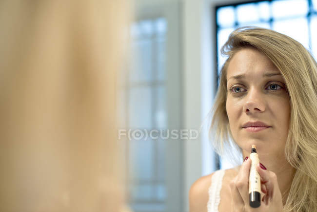 Portrait of Woman applying cosmetics looking in the mirror — Stock Photo