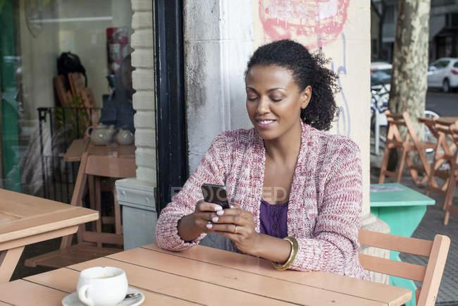 Mulher usando o telefone celular no café de calçada — Fotografia de Stock