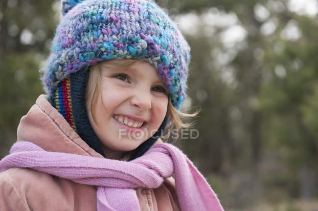 Bambina con cappello e sciarpa in maglia, sorridente, ritratto — Foto stock