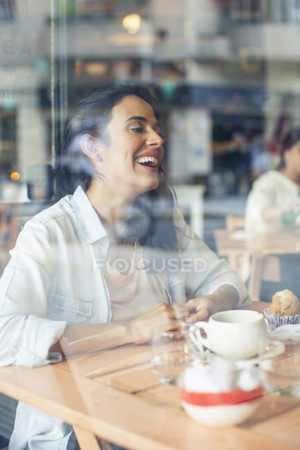 Сміється жінка в кафе — стокове фото