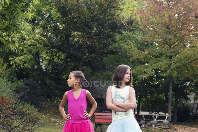 Girls standing together outdoors, both looking away angrily — Stock Photo