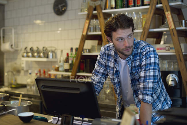 Cafe owner standing behind cash register — Stock Photo