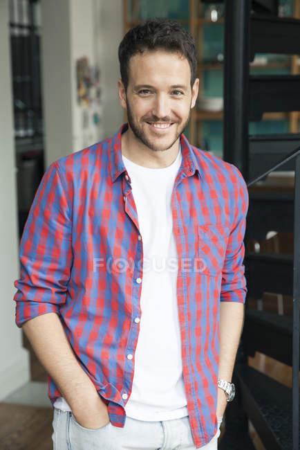 Ritratto di uomo barbuto sorridente con le mani in tasca — Foto stock
