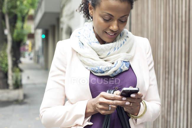 Afrikanerin benutzt Handy im Freien — Stockfoto