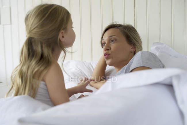 Madre e hija haciendo muecas en la cama - foto de stock