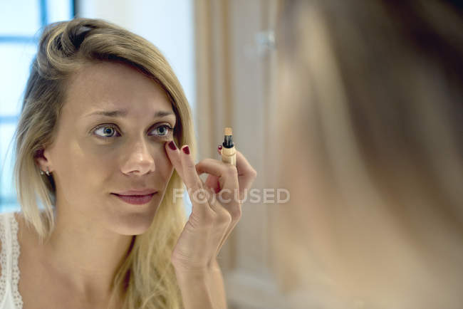 Woman applying cosmetics looking in the mirror — Stock Photo