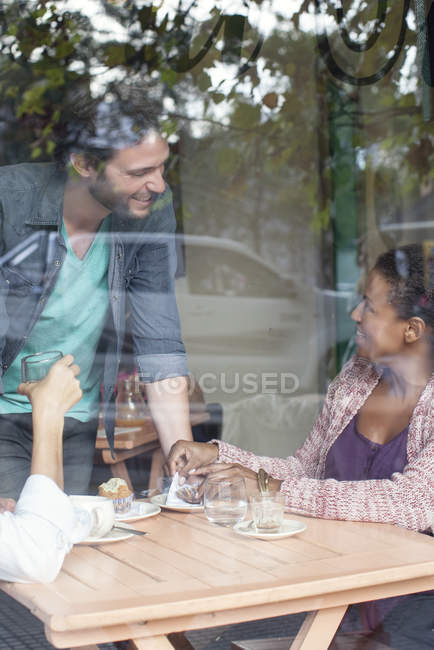 Waiter talking to customer in coffee shop — Stock Photo