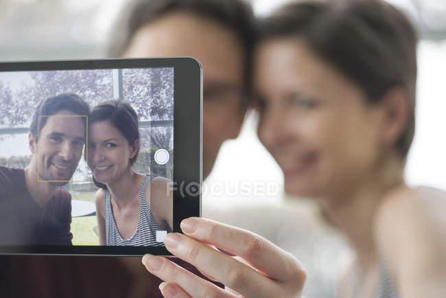 Casal usando tablet digital para tirar uma selfie — Fotografia de Stock