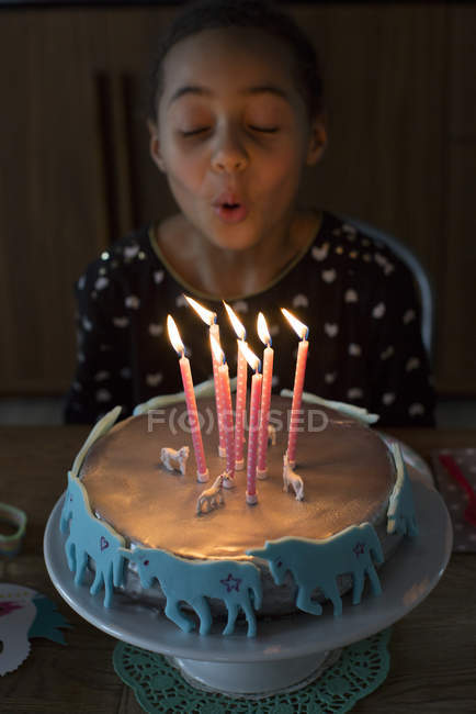 Girl blowing out candles on birthday cake — Stock Photo