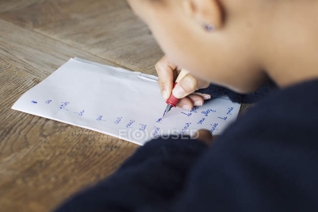 Girl writing in cursive on paper, cropped — Stock Photo