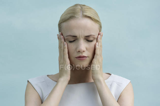 Woman holding face in hands, eyes closed — Stock Photo