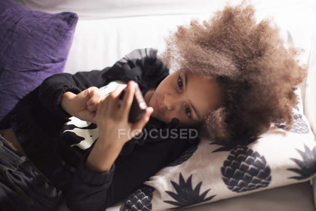 Ragazza sdraiata sul divano usando smartphone — Foto stock