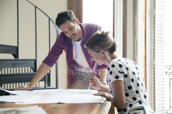 Wife and husband reviewing blueprints for home renovation — Stock Photo