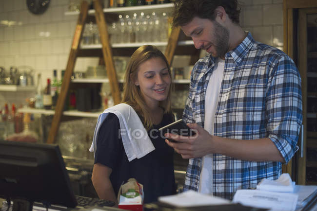 Restaurant employees at cash register — Stock Photo