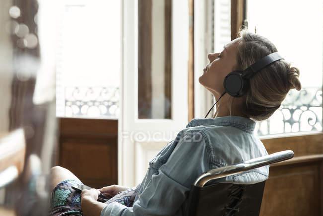 Donna che si distende durante l'ascolto di musica — Foto stock