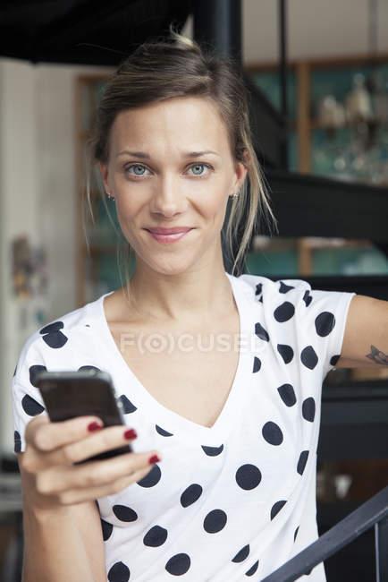 Donna sorridente tramite smartphone — Foto stock