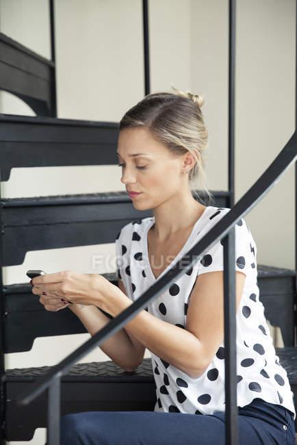 Testo di donna che si siede sulle scale di messaggistica — Foto stock