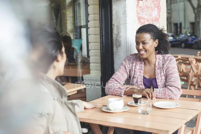 Жінка друзі говорили на тротуарі кафе — стокове фото